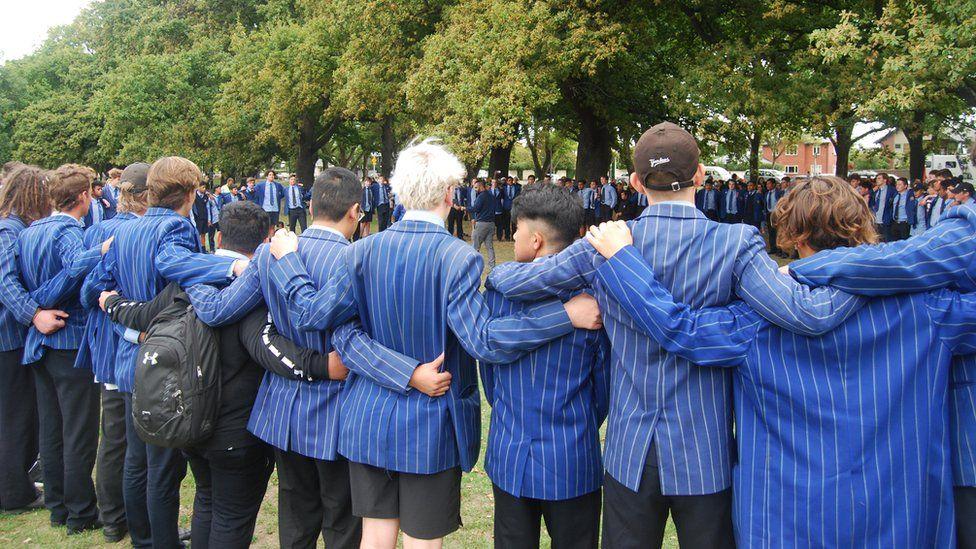 Schoolchildren link arms at a vigil in Christchurch