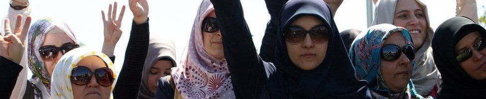 Women with headscarves and sunglasses, raising their hands in the air during a protest in Ankara on September 7, 2013 after the Middle East Technical University reportedly refused admission to students wearing headscarves.