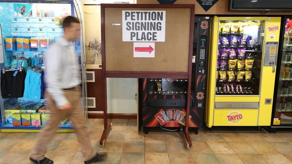 A man walks past signage for a recall petition at the Joey Dunlop Leisure Centre in Ballymoney