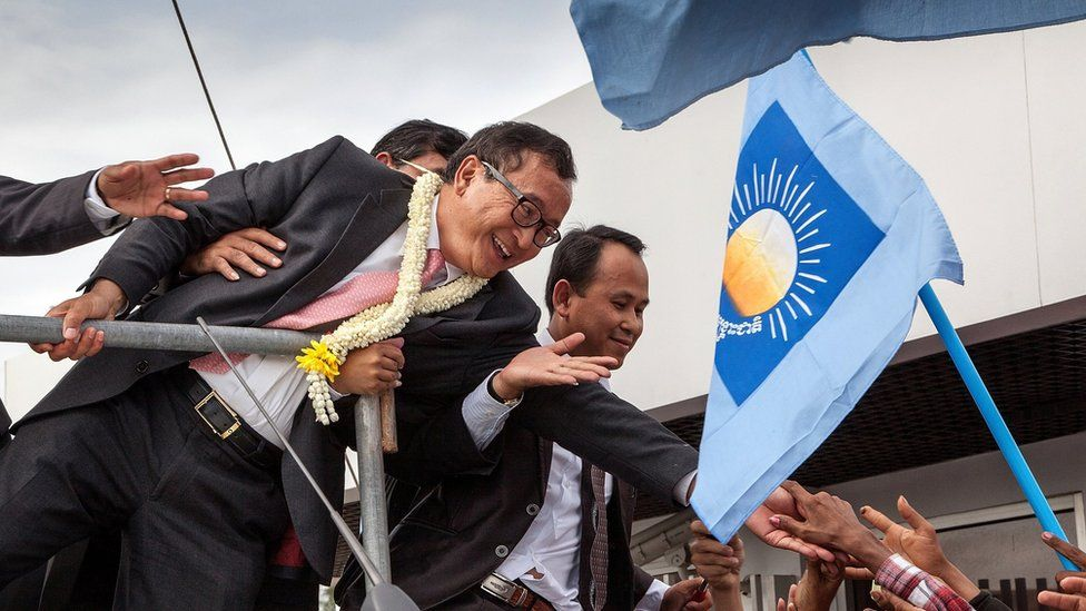 Cambodia National Rescue Party President Sam Rainsy greets supporters at Phnom Penh International Airport after arriving in Cambodia on July 19, 2014 in Phnom Penh, Cambodia