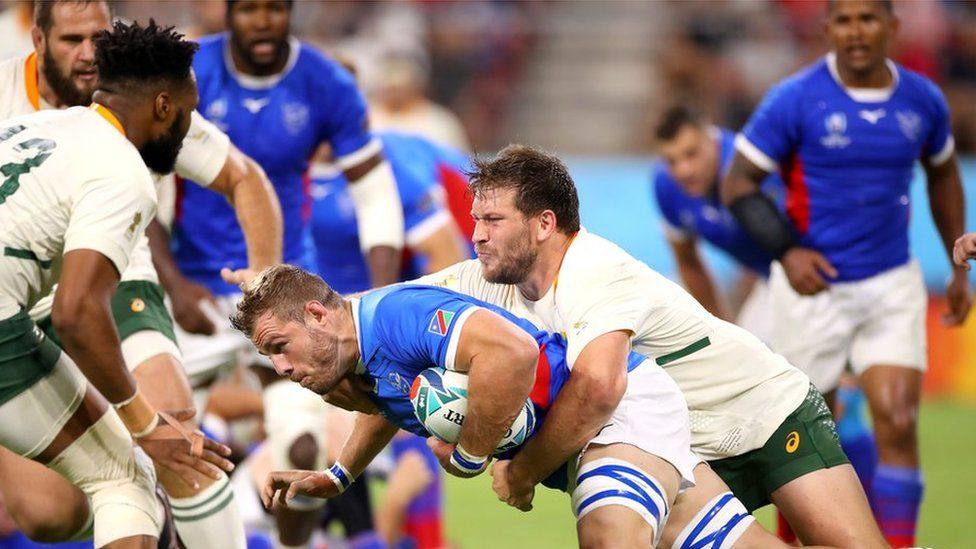 Namibian player Wian Conradie is tackled during a Group B game against South Africa.