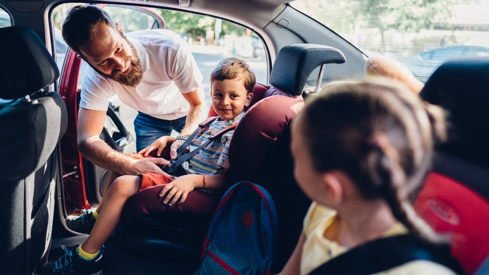 A man putting his children into car seats