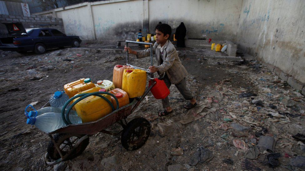 A boy pushes a wheelbarrow filled with water containers in Sanaa, Yemen (13 October 2017)