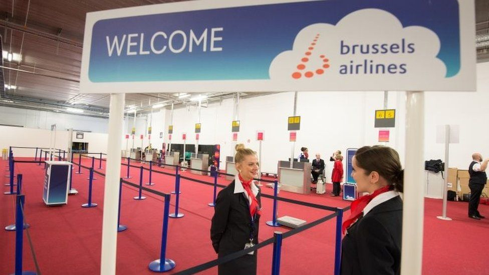 Representatives of Brussels Airlines await the first passengers as limited services resume