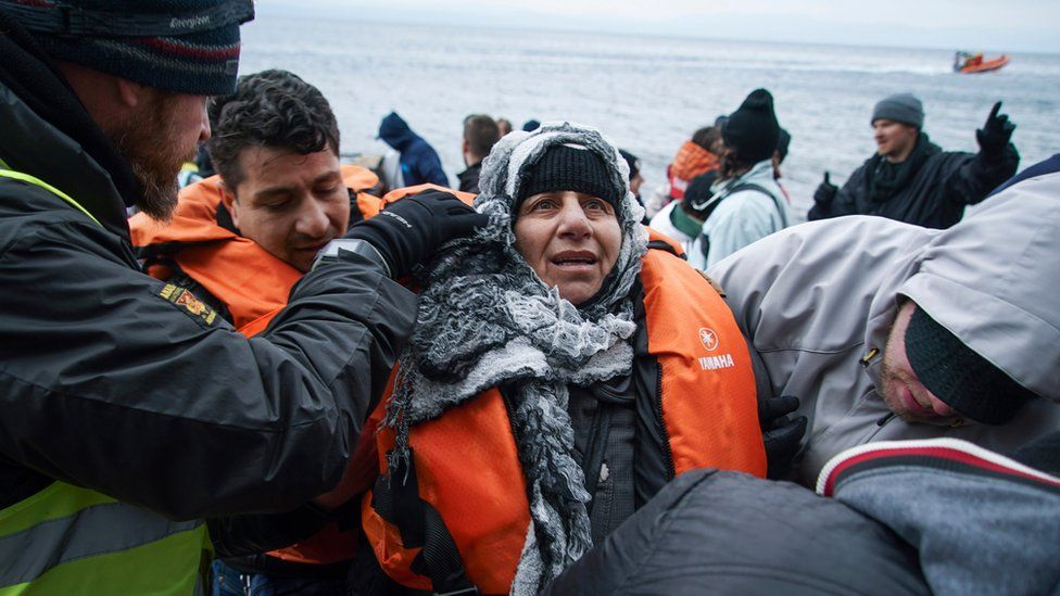 Volunteers help a woman who arrived on a dinghy with other migrants and refugees from the Turkish coast to the Greek island of Lesbos, on Tuesday, Jan. 26, 2016.