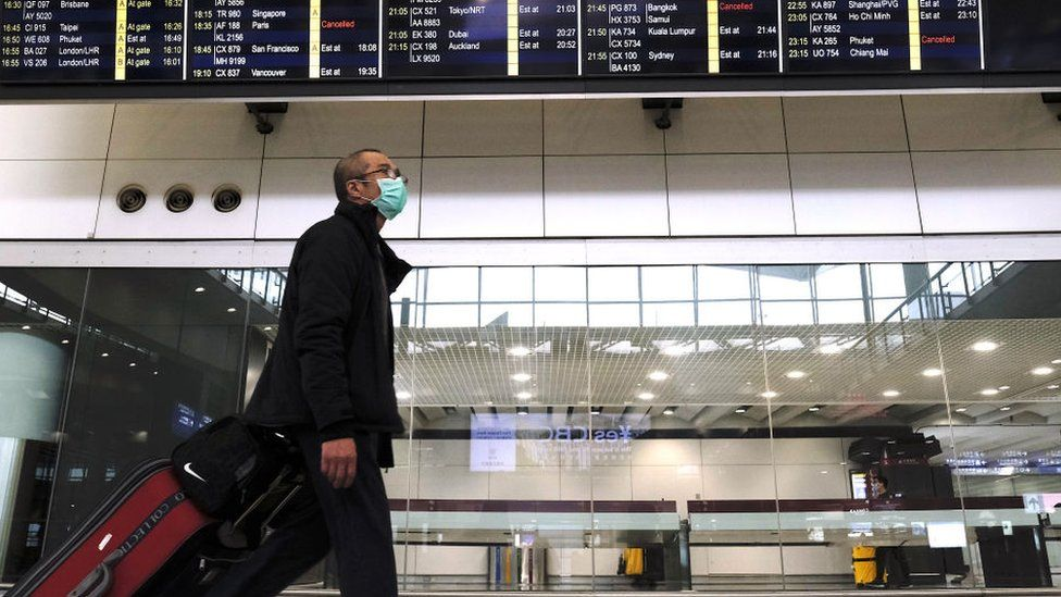 Aman wearing a mask pulls suitcase as he walks past a flight information display board