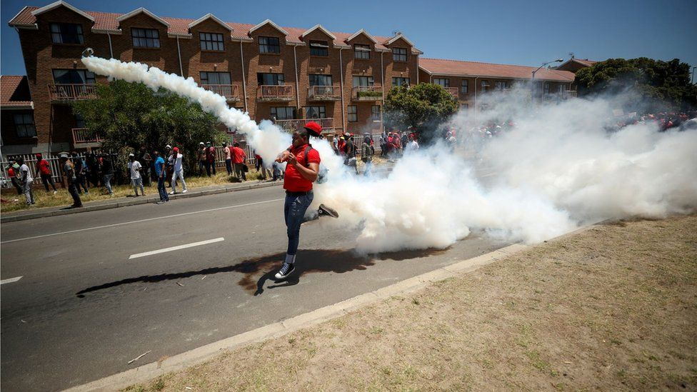 "A protester throws a teargas can back at the police during the opposition Economic Freedom Fighters party""s protest against alleged racism outside Brackenfell High School in Cape Town, South Africa, November 20, 2020."