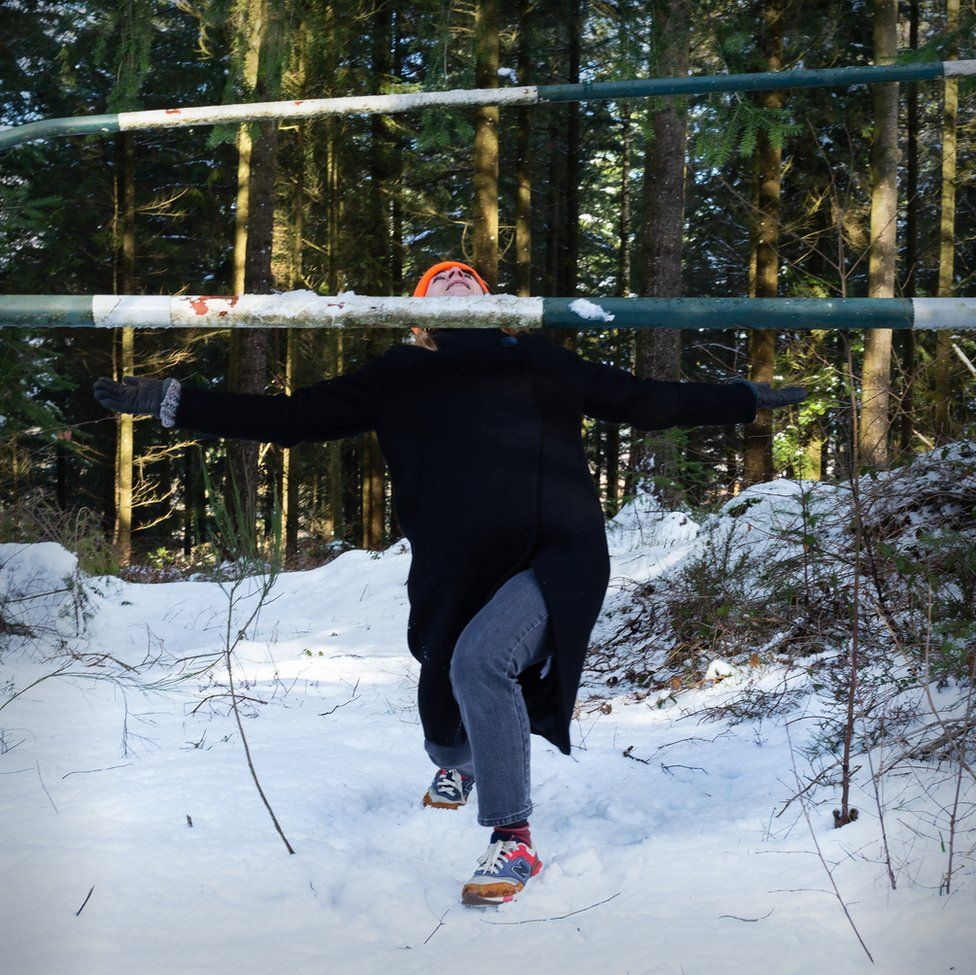 An image of a woman limboing a pole in a snow-covered forest