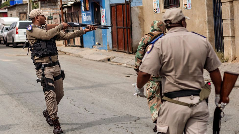 A police officer firing rubber bullets in Alexandra, South Africa - Tuesday 31 March 2020