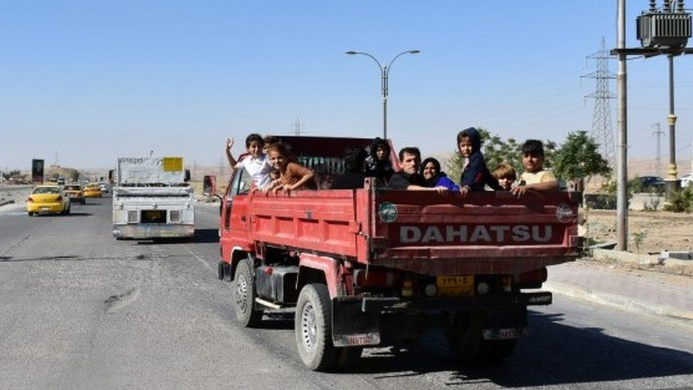 Kurdish families, who fled their homes in Kirkuk the day before, pass through a checkpoint as they make their way back to their homes (17 October 2017)