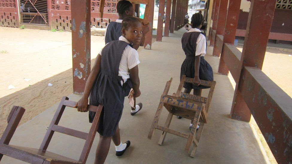 Children dragging chairs to calss