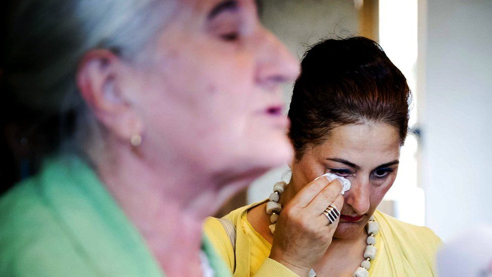 A woman wipes a tear away outside court in the Netherlands