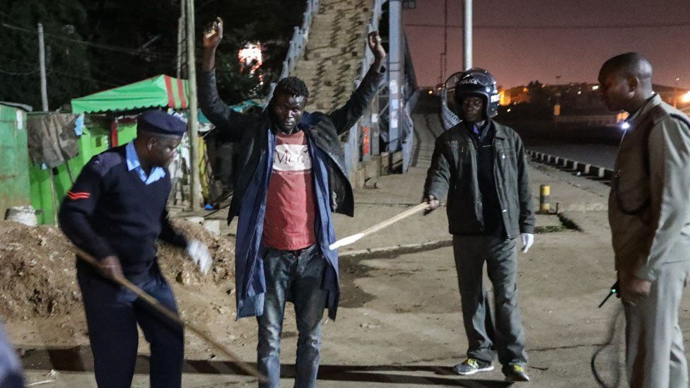 Kenyan police officers interrogate and conduct a body search on a man (C), whom they found walking at night as they patrolled