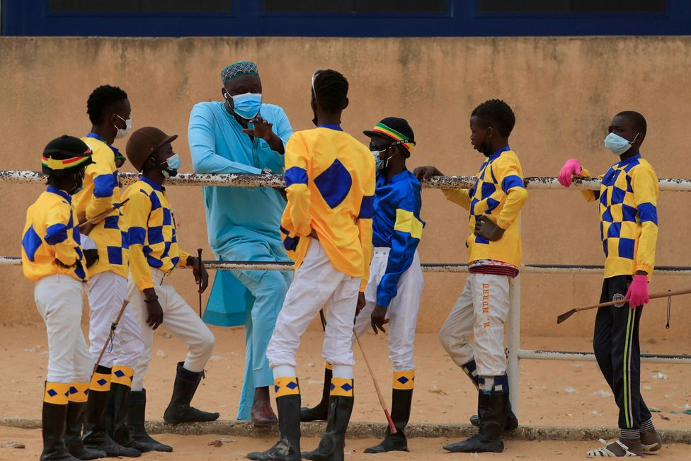 Adama Bao, a coach who owns the Lambafar stable, speaks to Fallou Diop and other jockeys before a race at in Thies, Senegal, 31 January 2021