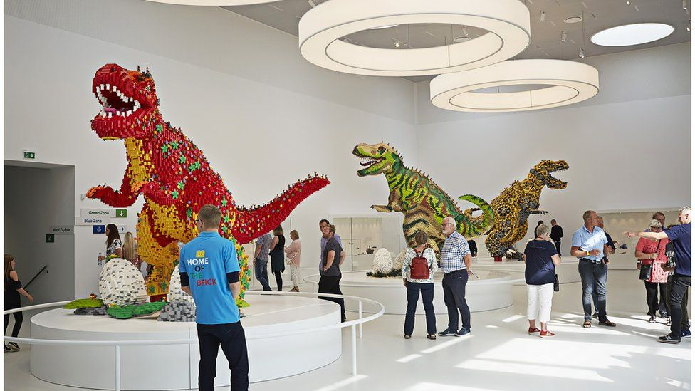 People look at dinosaurs in the Masterpiece Gallery at Lego House