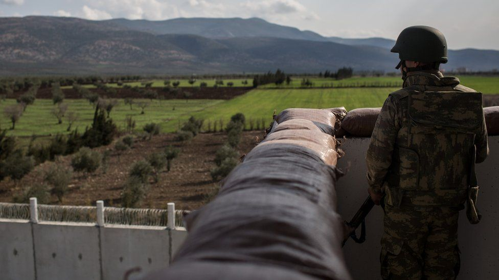 A Turkish soldier looks out over the border wall to Syria