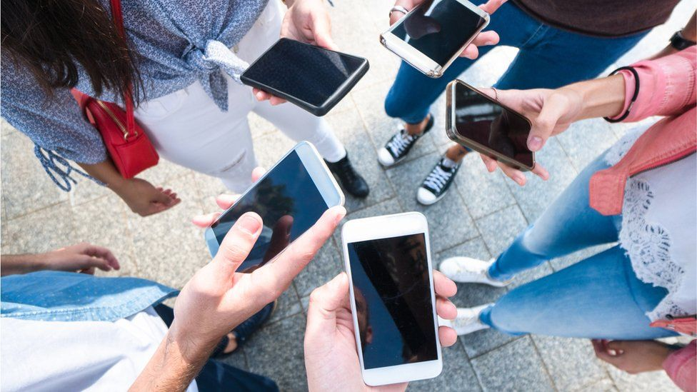 File picture of people using mobile phones