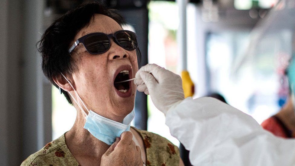 A medical worker takes samples during a mass Covid-19 test in Wuhan