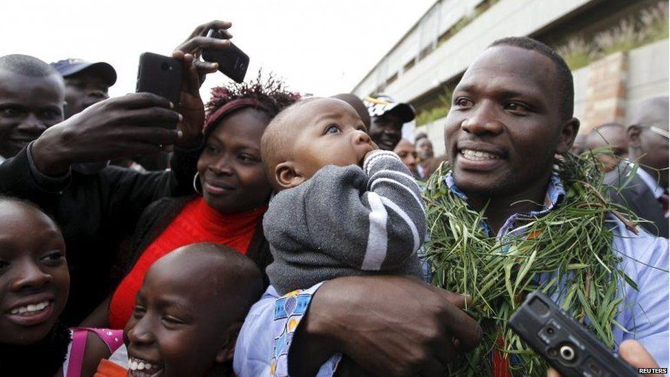 IAAF men's javelin throw gold medallist Julius Yego of Kenya carries his son after arriving at the Jomo Kenyatta airport in Nairobi