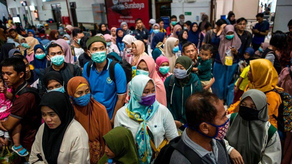 Indonesians wear masks at transport hub.