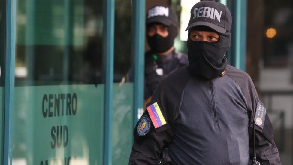 Members of the Sebin intelligence service stand outside the building housing the office of Venezuela's opposition leader Juan Guaidó in Caracas, 21 January 2019