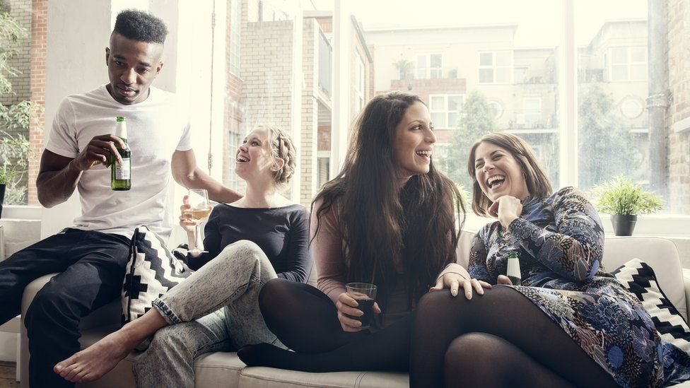 A group of friends at a house party drinking, before the coronavirus pandemic.