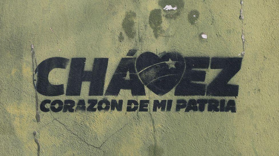 "A stencil on a wall reads ""Chávez, the heart of my homeland"""