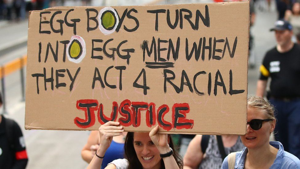 """A protester in Melbourne holds a placard reading: """"Egg Boys turn into egg men when they act 4 racial injustice"""""""
