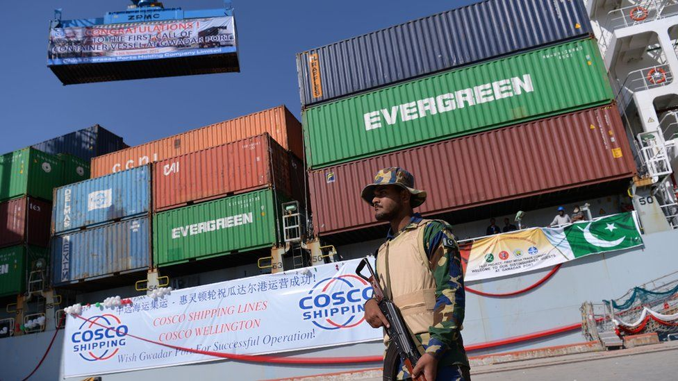 A Pakistani Naval personnel stands guard beside a ship carrying containers during the opening of a trade project in Gwadar port, some 700 kms west of Karachi on November 13, 2016