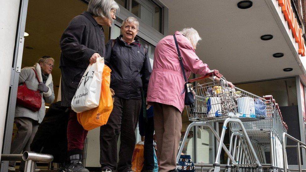 Elderly shoppers outside Sainsbury's