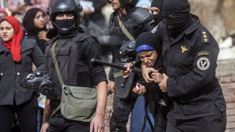 An Egyptian riot policeman detains a female student at al-Azhar University during a protest inside their campus in Cairo on 30 December 2013