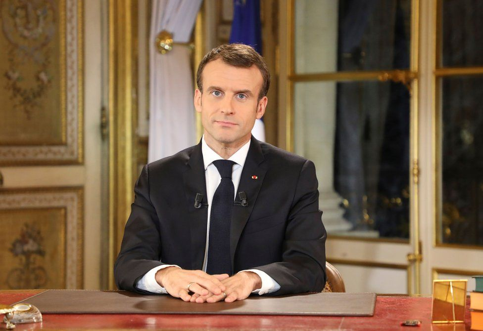 Emmanuel Macron sits at a desk in the Elysee Palace