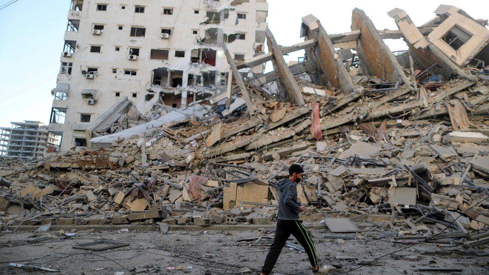 Seorang pria Palestina berjalan melewati gedung bertingkat tinggi yang hancur dalam serangan udara Israel di Kota Gaza 12 Mei 2021