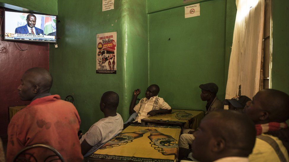 Men watch opposition candidate Raila Odinga speak at a news conference in a bar in the Mathare North neighbourhood