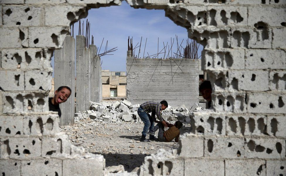 Boys play near remains of war-damaged buildings in the rebel-held Damascus suburb of Douma (19 March 2016)