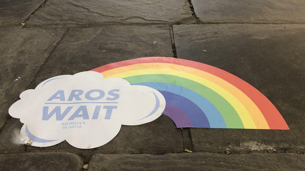 A rainbow sticker on the floor of the arcade