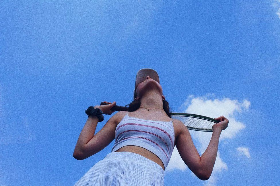 A girl looks up at the sky with her tennis racket