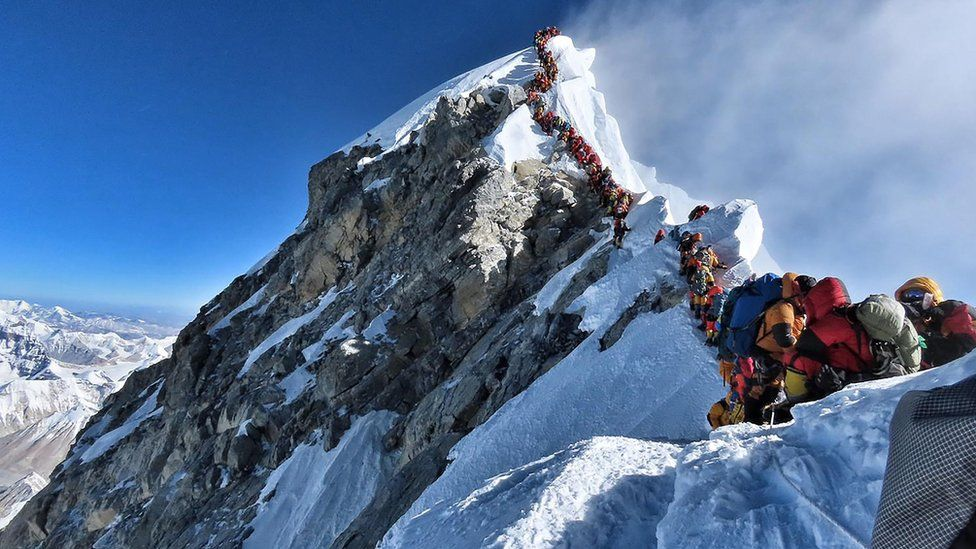 Heavy traffic of mountain climbers lining up to stand at the summit of Mount Everest.