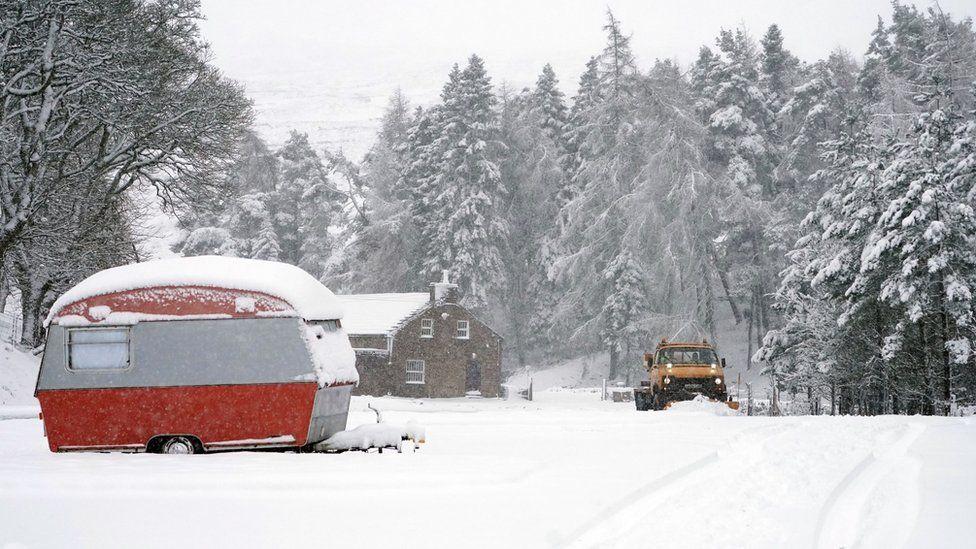 A snow plough passes an old caravan in Nenthead, Cumbria