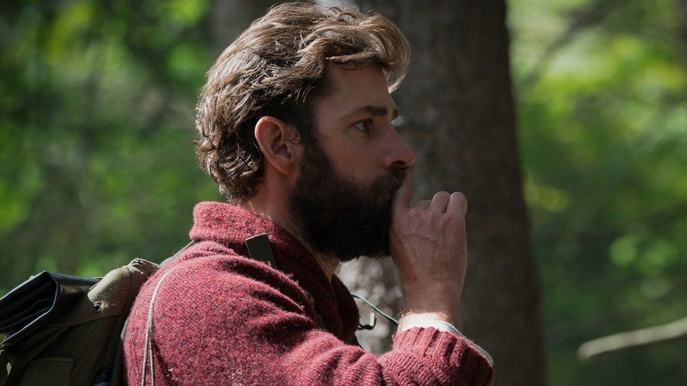 John Krasinski hushing with fingertip in still from the film