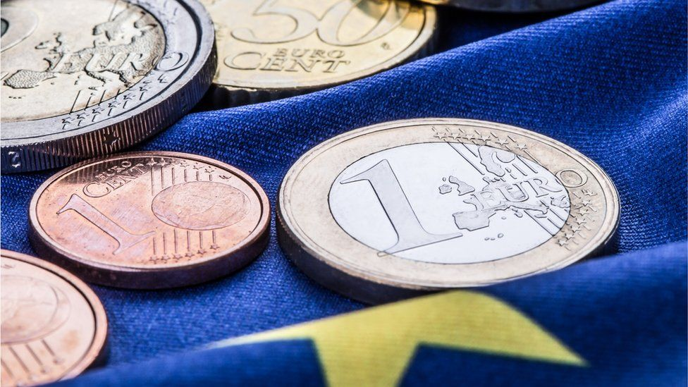 Euro coins pictured on a European flag