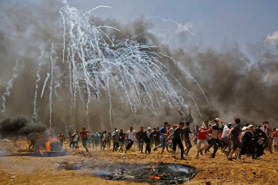 Palestinians run for cover from tear gas during clashes with Israeli security forces near the border between Israel and the Gaza Strip, east of Jabalia on 14 May 2018.