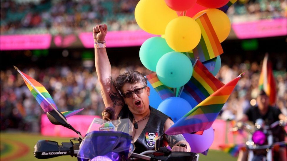 A female biker, with her fist in air, rides with rainbow flags and balloons in front of the crowd