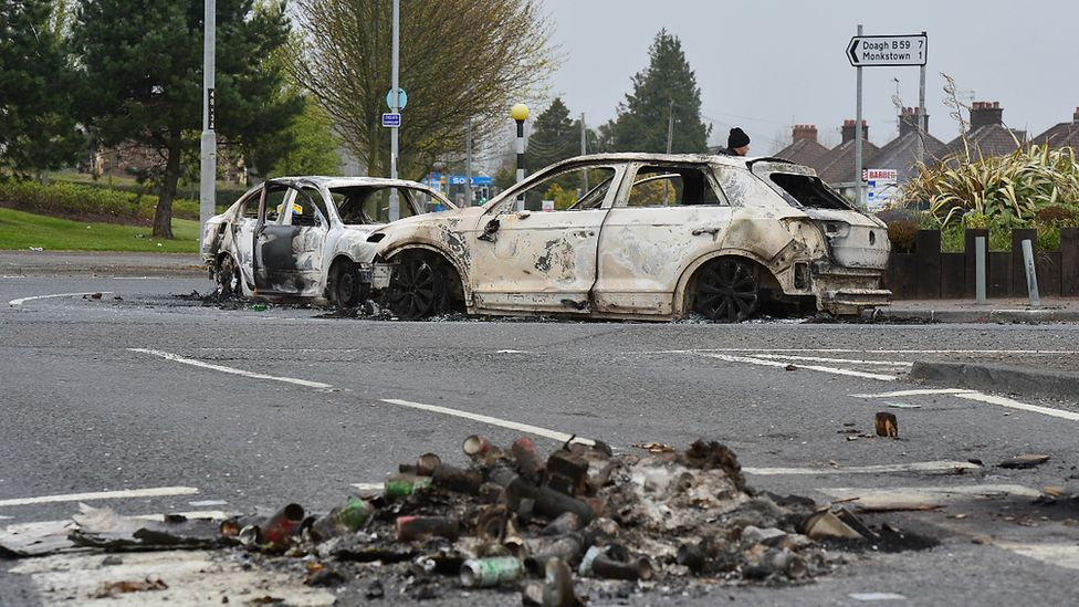 Burnt out cars remain on the road on 4 April following violence in Newtownabbey the night before