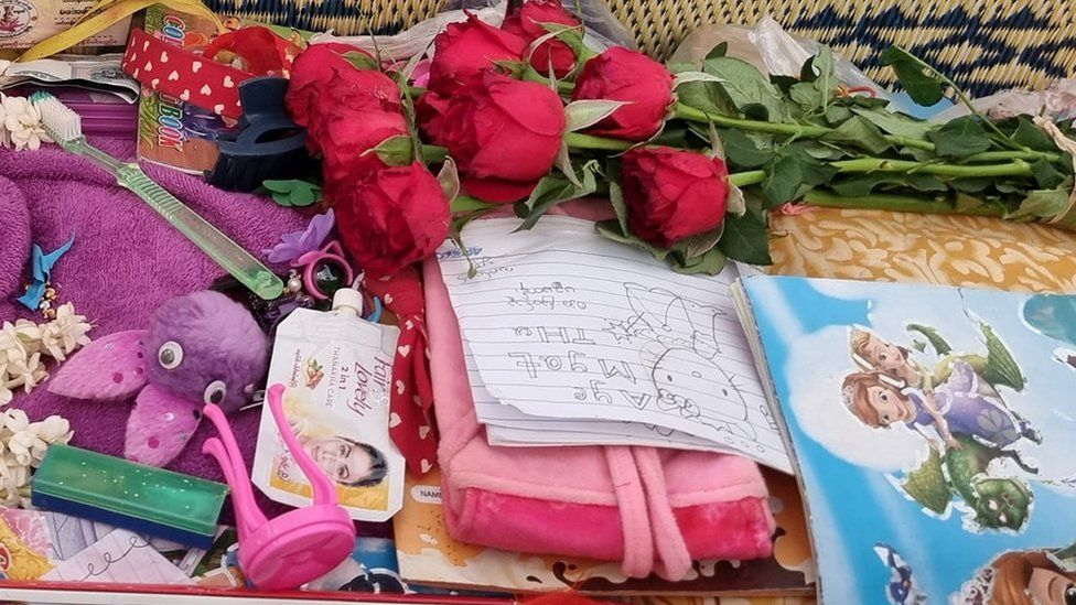 Toys flowers and drawings are seen in Aye Myat Thu's coffin