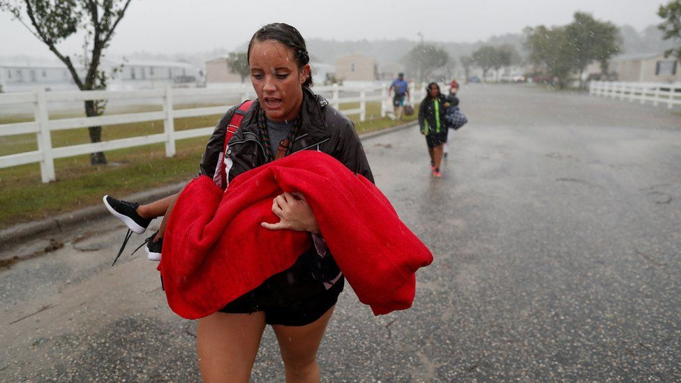 Maggie Belgie of The Cajun Navy carries a child evacuating a flooding trailer community during Hurricane Florence in Lumberton, North Carolina, 15 September 2018