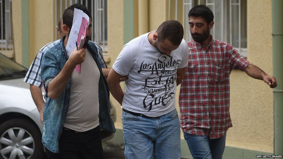 Turkish plainclothes police officers escort a suspected member of the Islamic State (IS) group at a hospital for a medical check-up on 24 July 2015 in Istanbul.