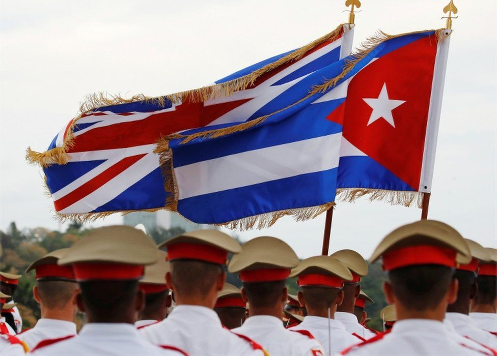 Union Jack and Cuban Flag flutter in the air above the guards