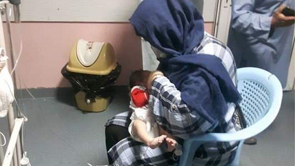 Firooza Omar breastfeeding a baby in a Kabul hospital