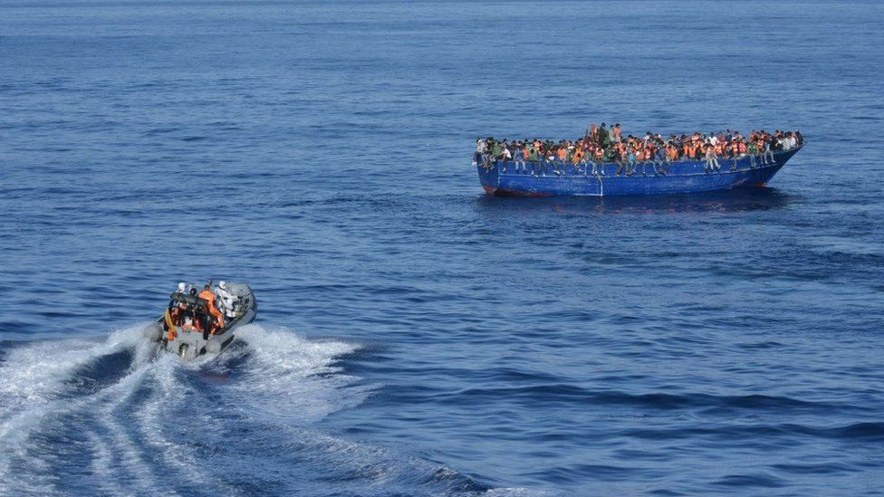 Spanish rescuers approaching a boat with migrants off the coast of Libya